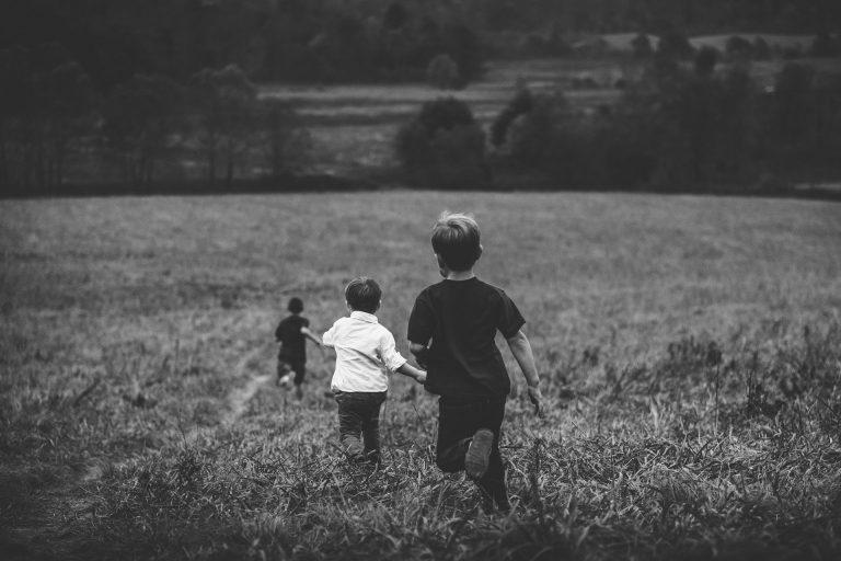 Barn springer på en äng